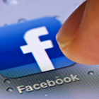 Facebook app icon, mobile device screen, index finger touching