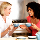 two women talking, two women smiling, two women drinking cup of coffee or tea